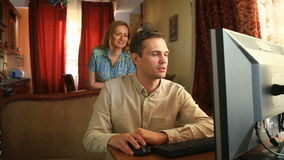 Working on the computer at home, her husband is satisfied with the successful transaction, his wife is satisfied with.  stock footage
