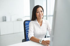 Working on computer. Smiling Chinese business lady working on computer Royalty Free Stock Photo