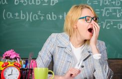 Working conditions for teachers. Work far beyond the actual school day. Woman tired teacher sit table classroom. Chalkboard background. Working conditions which royalty free stock images