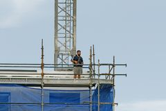 Working construction crane. Update ? . Gosford. January 2019. Gosford, New South Wales, Australia - January 31, 2019: Crane operator remotely controlling a royalty free stock photo