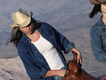 Working Cowgirl. Cowgirl walking through Nevada desert holding a saddle royalty free stock photography