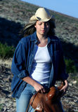 Working Cowgirl. Cowgirl walking through the desert olding a saddle Royalty Free Stock Photos
