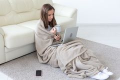 Working, cozy, people concept - young woman working at home in plaid, drinking tea and chatting in netbook royalty free stock image