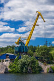 Working crane on the dock. Yellow crane on the dock worker loading rubble Royalty Free Stock Photos
