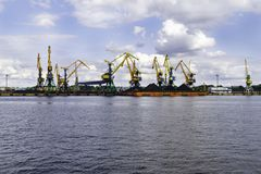 Working crane in the port, The Cargo in the Port Pier at the Loading of Coal. Industrial view. Working crane in the port, The Cargo in the Port Pier at the royalty free stock photography