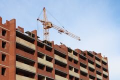 Working crane and red brick residential building Stock Image