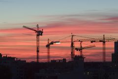 Working Cranes. Sunset with cranes working on a construction place Stock Photos