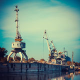 Working cranes for cargo at the shipyard docks in river port. Stock Photography
