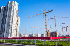 Working cranes are under blue sky. Block of flats under construction, working cranes are under blue sky Royalty Free Stock Images