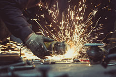 Working on cutting a metal tube with a sharp angle grinder with circular blade and generating sparks Stock Photos