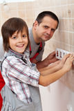 Working with dad - boy helping his father. Installing electrical wall fixtures, mounting decorative frame Royalty Free Stock Photo