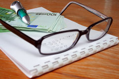 After a working-day. Office desktop with pen, book, eye-glasses and money stock photo