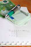 After a working-day. Office desktop with pen, book and money royalty free stock image