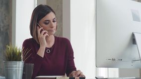 Working day: beautiful woman speaks on the phone, sitting at desk. In a bright modern office. A modern woman makes a career, works in the office as a manager or stock video footage