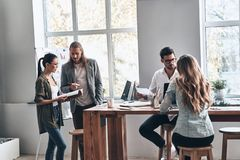 Working day. Group of young modern people in smart casual wear discussing business while working in the creative office stock photography
