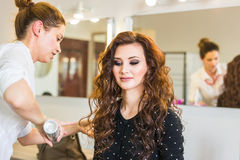 Working day inside the beauty salon. Hairdresser makes hair styling. Royalty Free Stock Photo