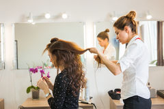 Working day inside the beauty salon. Hairdresser makes hair styling. Royalty Free Stock Image