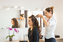 Working day inside the beauty salon. Hairdresser makes hair styling. Stock Photos