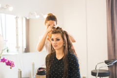 Working day inside the beauty salon. Hairdresser makes hair styling Stock Images