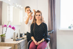 Working day inside the beauty salon. Hairdresser makes hair styling Stock Photography