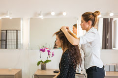 Working day inside the beauty salon. Hairdresser makes hair styling Royalty Free Stock Photography