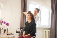 Working day inside the beauty salon. Hairdresser makes hair styling Stock Image