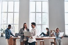 Working day in office. Group of young modern people in smart casual wear smiling and discussing something while working in the creative office stock photo
