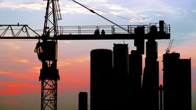 The working day is over. People talking while sitting on a high-rise crane afterhours Stock Image