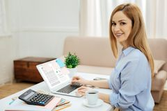 Inspired businesswoman working from home. Working day. Pretty alert young blond long-haired woman wearing a blue shirt while working on her laptop and calculator Stock Image