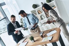 Working day. Top view of young modern people in smart casual wear discussing business while standing in the creative office royalty free stock images