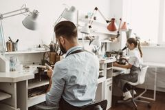 Working day in workshop. Jewelers team are working together at jewelry making workshop. Business stock images