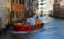 Working delivery boat on Venice canal. VENICE, ITALY - SEPTEMBER 25, 2017: Working delivery boat on Venice canal Royalty Free Stock Image