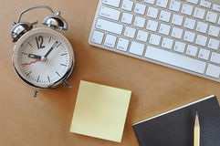 Working desk with alarm clock, keyboard, sticky note, book and pencil Royalty Free Stock Photos