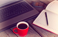 Working desk with cup of coffee planner agenda laptop and mobile phone vintage morning Stock Images