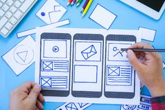 Working desk with hands sketching of screens for mobile responsive website development with UI/UX. Developing wireframe sketch royalty free stock photography
