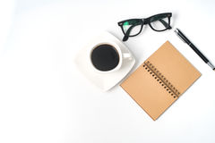 Working desk table with notebook, pen, pencil and cup of coffee. Royalty Free Stock Image