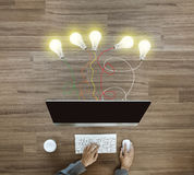 Working on desktop computer with creative light bulb ideas Stock Images