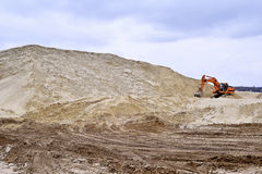 Working digger in a quarry produces sand.  Stock Image