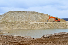 Working digger in a quarry produces sand.  Royalty Free Stock Photo