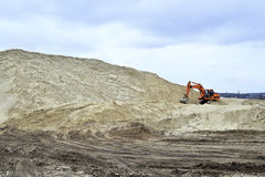 Working digger in a quarry produces sand.  Royalty Free Stock Images
