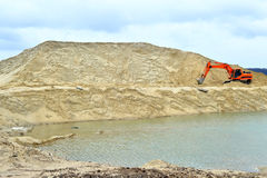 Working digger in a quarry produces sand.  Stock Photos