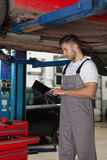 Working on a Digital Tablet in Auto Repair Shop Stock Images