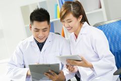 Working doctors. Two young doctors working together and laughing Stock Image