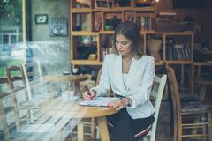 Working on document. Young business woman writing on document at cafe stock photo