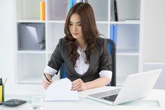 Working with documents. Pretty manager signing documents in her office Stock Photography