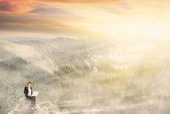 Working at dream. Business woman working at dream with beautiful misty mountain landscape under dramatic sunlight. Photo compilation concept about business Stock Image