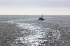 Working dredger in in Wadden Sea near Ameland island Royalty Free Stock Photos