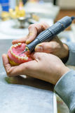 Working with a drill in a dental prosthesis. In a dental laboratory Royalty Free Stock Photos