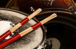 Working drum with drum sticks, musical instrument. On black background Stock Photos