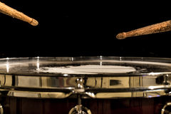 Working drum with drum sticks, musical instrument. On black background Royalty Free Stock Photography